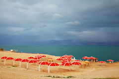 Red umbrellas and green sea Stock Images