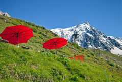 Red umbrellas and lounges in mountain cafe Royalty Free Stock Photo