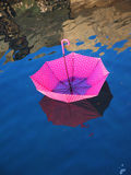 Red upturned umbrella floating on water surface Stock Images