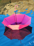 Red upturned umbrella floating on water surface Stock Photo