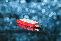 Red USB flash memory on blue background out of focus Royalty Free Stock Photo