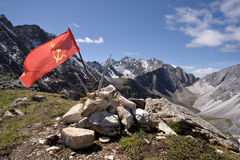 Red USSR flag at the top of mountain among stones Royalty Free Stock Images