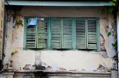 Red ut blåa gröna träslutare på fönster med texturerad skalande målarfärg Kuching Malaysia royaltyfria foton