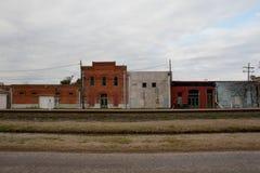 Red ut byggnader längs järnväg i lantliga Texas Town Arkivfoto