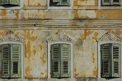 Red ut fönsterslutare av ett övergett hus, med utsmyckade detaljer och gå i flisor målarfärg Arkivfoton
