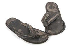 Red ut par av utslitna svarta lädersandaler Royaltyfria Foton