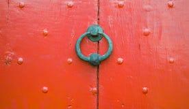 Red ut röda trädörren för bakgrund spikar stryker den textur med garnering och den runda dörrknackaren Royaltyfria Bilder