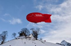 Red Valais Blimp Above White Wooden House Stock Image