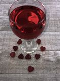 Valentine`s Day heart and wine on wood background. Red Valentine candy hearts at base of wine glass with red wine on gray wood board background royalty free stock photography