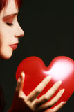 Red valentine heart. Beautiful woman face and red valentine heart on a black background Stock Photography