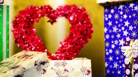 Red valentine heart inside gift box. Red big decorated heart inside present cox at colorful background stock footage