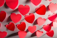 Red Valentine Hearts. A display of small, randomly positioned red valentine hearts on a grayish, shadowy background Royalty Free Stock Photography