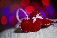 Red Valentine hearts with bokeh background. Christmas decoration, hand made toy Stock Photos