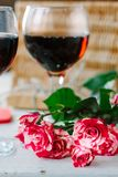 Red Valentine's day roses and glass of wine on white table.  stock images