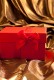 Red Valentines gift nestling in gold fabric Royalty Free Stock Photos
