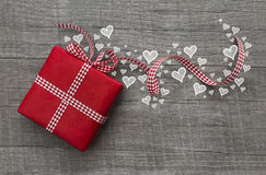 Red valentines present with checked ribbon and hearts on grey wo Royalty Free Stock Photos