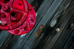A red valve on the wooden deck of a battleship. Royalty Free Stock Photos
