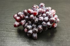 A red variety of grapes. A red variety of grapes on a wooden table Stock Photography