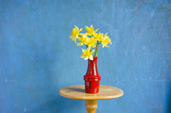 Red vase with spring narcissus on table Stock Image