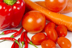 Pepper, carrots, tomatoes, sweet tomatoes and chil. Group of red veggies such as bell pepper, carrots, tomatoes, sweet tomatoes and chili. Closeup Stock Images