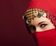 The red veil. A beautiful woman wearing a red exotic veil Royalty Free Stock Photo