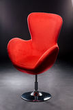 Red velour seat on the Nickel-plated steel leg in the Studio on a black background. Comfortable office chair red. Stock Images