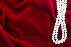Red velvet background with pearls Royalty Free Stock Photography