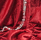 Red velvet and beads. Red velvet and a string of beads Royalty Free Stock Photography