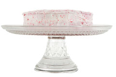 Red velvet cake. With pink frosting on a serving tray isolated over white Royalty Free Stock Images