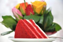 Red velvet cake. Slice of red velvet cake on plate with roses in the background stock photo