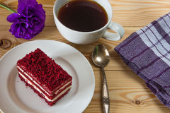 Red velvet cake, cup of coffee and purple flower on wooden back Stock Photo