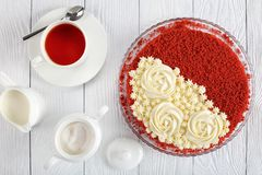 Red velvet cake and cup of tea. Delicious red velvet cake topped with beautiful creamy roses and sprinkled with red sponge cake crumbs on plate on white wooden royalty free stock images