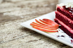 Red velvet cake on plate decorated with sliced apple Royalty Free Stock Photo