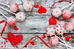 Red velvet cake pops covered in white chocolate decorated with red and pink sugar sprinkles for valentine day. Red velvet cake pops covered in white chocolate royalty free stock photos