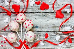Red velvet cake pops covered in white chocolate decorated with red and pink sugar sprinkles for valentine day. Red velvet cake pops covered in white chocolate stock photos