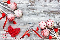 Red velvet cake pops for valentine day. Red velvet cake pops covered in white chocolate decorated with red and pink sugar sprinkles, sweet treats for valentine royalty free stock images