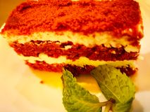 Red velvet cake on a white plate, and decorated with mint leaves.  Royalty Free Stock Photo