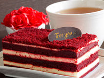 Red velvet cake on wood table and red roses. Slice of Red velvet cake on wood table and red roses Royalty Free Stock Images