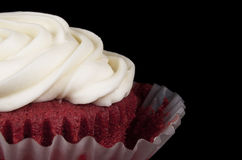 Red Velvet Cupcake. A delicious red velvet cupcake with swirled cream cheese icing in a pulled away paper wrapper on a black background Stock Images