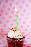 Red velvet cupcake with green wavy candle royalty free stock images