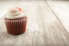 Red velvet cupcake on rustic table top. A red velvet cupcake on a white washed table Royalty Free Stock Photography