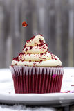 Red Velvet Cupcake in Snow with Heart Sprinkling Down Royalty Free Stock Images