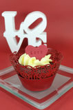Red velvet cupcake with vanilla frosting and cute red hearts with love message Royalty Free Stock Photo