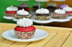 Red Velvet Cupcake. A red velvet cupcake with vanilla frosting with various cupcakes on the background Royalty Free Stock Photos