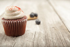 Red velvet cupcake and wooden spoon with blueberries. A red velvet cupcake on a white washed table with wooden spoon and blue berries Stock Photos
