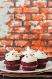 Red velvet cupcakes with cream cheese frosting. On a white plate royalty free stock image
