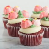 Red Velvet Cupcakes With Edible Buttercream Flowers. On White Marble Table stock photo