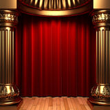 Red velvet curtains behind the gold columns Stock Photos