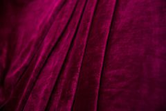 Red velvet fabric folded in an accordion, lies on the table view diagonally, folds on the fabric royalty free stock images