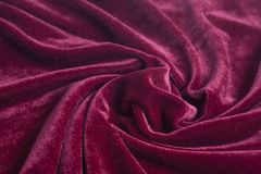 Red velvet fabric with spiral folds. Closeup royalty free stock photos